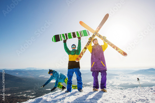 Poster Wintersporten Happy Skier and snowboarder friends standing on mountain top with ski and snowboard in hands
