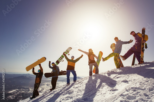 plakat Group of people snowboarders and skiers on mountain sunset. Winter Sport outdoor