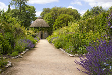 The 19th Century Thatched Round House Surrounded By Beautiful Flower Beds And Gravel Paths In The Walled Garden At West Dean Gardens In Hampshire, England