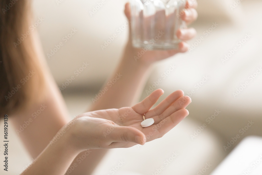 Fototapeta Close up photo of one round white pill in young female hand. Woman takes medicines with glass of water. Daily norm of vitamins, effective drugs, modern pharmacy for body and mental health concept