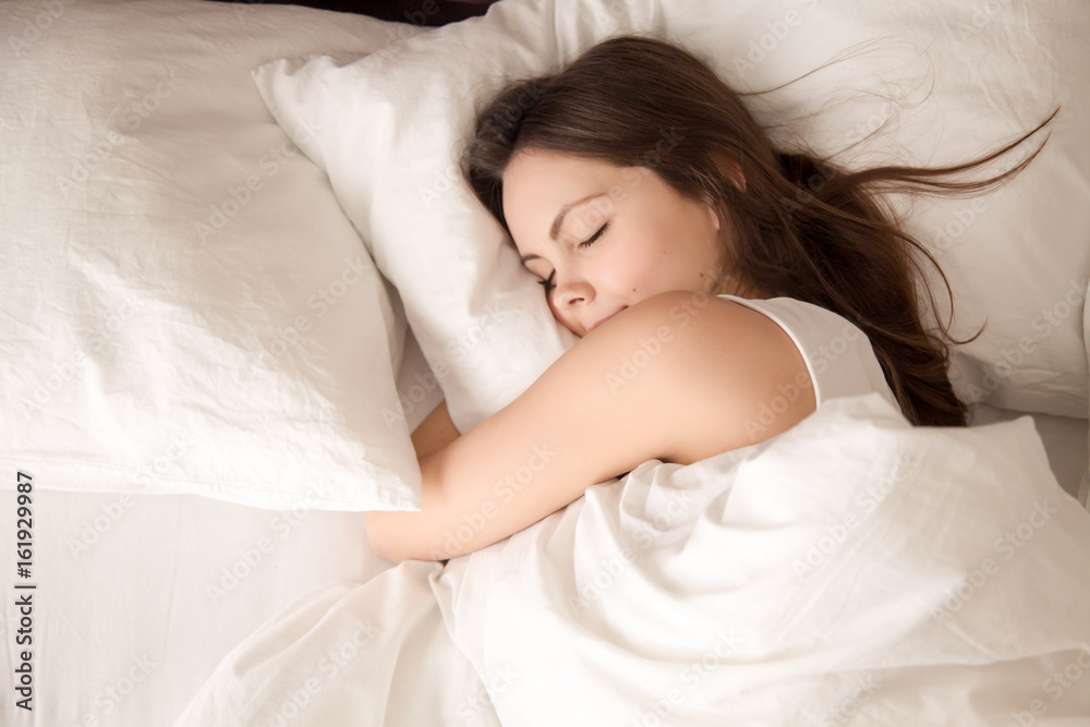 Fototapeta Top view of attractive young woman sleeping well in bed hugging soft white pillow. Teenage girl resting, good night sleep concept. Lady enjoys fresh soft bedding linen and mattress in bedroom