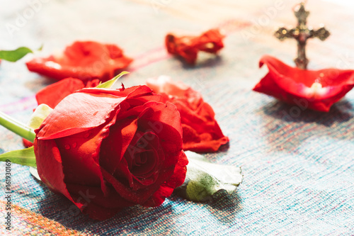 фотография  Bright Red Rose with blur metal cross god background