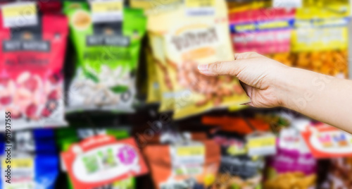 Fotografering  hand of woman choosing or taking sweet products, snacks on shelves in convenienc
