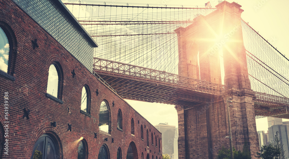 Fototapeta Brooklyn Bridge at sunset with lens flare, color toning applied, New York City, USA.