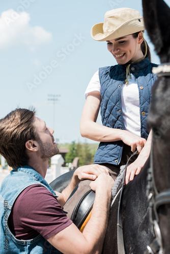 Fototapeta Handsome young man looking at smiling woman sitting on horseback obraz na płótnie
