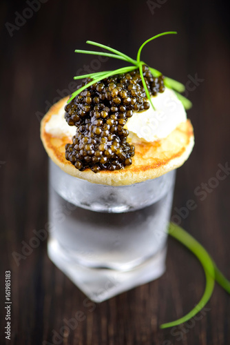 Russian Pancakes Blini with Sour Cream and Black Caviar Served on Vodka Shot.