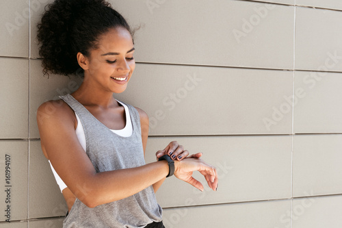 Fotografía Fitness woman taking a break, checking activity tracker