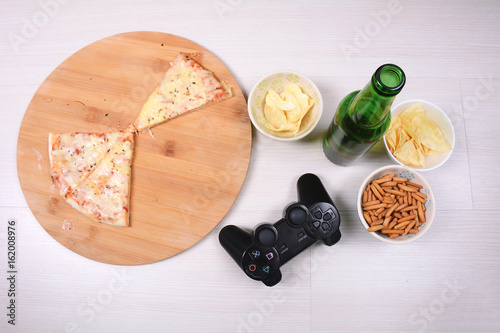 Photo  Pizza, snacks and beer with joystick.