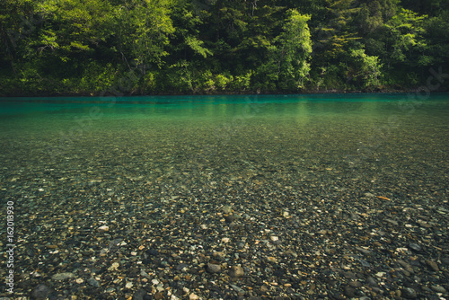Poster Kaki Turquoise river in a forest.