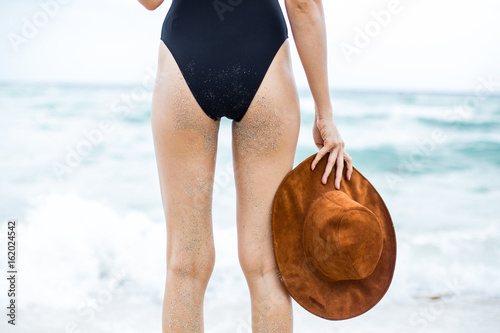 Photo  summer bum with a hat on hand