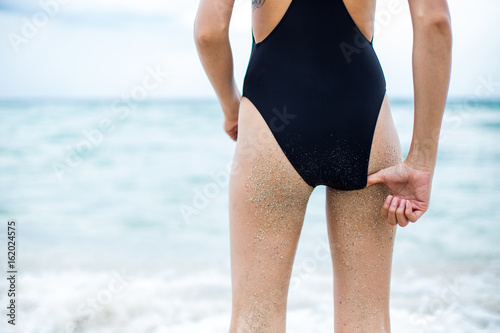 Pulling the swimsuit out from woman's bum Poster