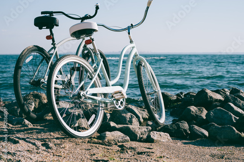 Deurstickers Fiets Two retro bike on the beach against the blue sea