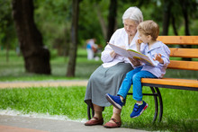 Young Boy And Great Grandmother Reading Book In Summer Park