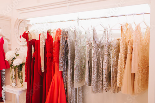 Grate choice of gorgeous fashion dresses hanging on racks in woman's wardrobe Fototapeta