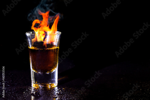 Foto op Canvas Alcohol Hot alcoholic cocktail burning in shot glass.
