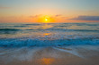 Sunrise over sea and sandy beach in spring