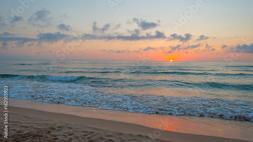 Fotobehang Zee zonsondergang Sunrise over sea and sandy beach in spring