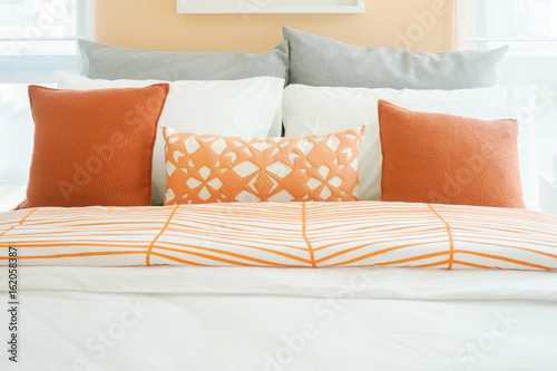 Modern bedroom interior with roll of orange, white and gray ...