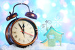canvas print picture - Alarm clock and Christmas decorations in snow on bright background