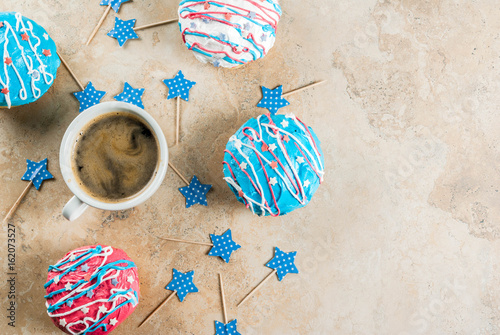 Food for independence day. 4th of July. Festive breakfast: traditional American donuts with glaze in colors of USA flag blue, red, white. Cup of coffee. On light stone table. Top view copy space