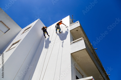 Photo industrial alpinist work on white wall
