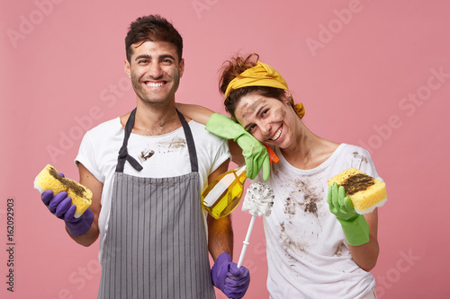 Obraz Housewife and her husband standing close to each other holding sponge, brush and cleaning solution having fun after cleaning room besmearing each other. Happy couple after cleaning their house - fototapety do salonu