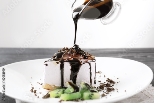 Fotografia  Pouring chocolate sauce onto plate with tasty cake on table, closeup