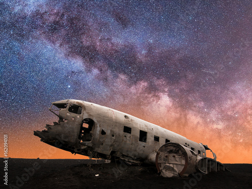 Valokuvatapetti Milky Way Galaxy Behind Mysterious Wreckage of a Crashed DC-3 Airplane