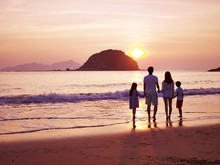 Asian Family Watching Sunrise On Beach