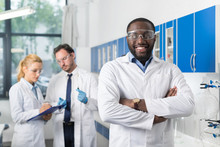Happy Smiling African American Scientist Stand In Front Of Colleagues In Laboratory Making Notes Of Experiment Or Research Results, Mix Race Team In Modern Science Lab
