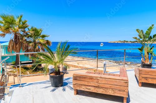 Benches on coastal promenade in San Antonio town on sunny summer day, Ibiza isla Wallpaper Mural