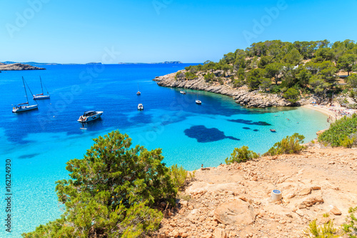 Fototapeta View of beautiful beach in Cala Salada bay famous for its azure crystal clear se