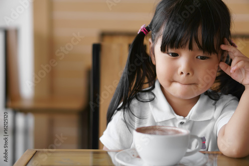 Asian children cute or kid girl has dimple and hot cocoa or chocolate drinking i Canvas-taulu