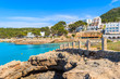 Rocks on coast of Cala Portinatx bay with hotels and restaurants in background, Ibiza island, Spain
