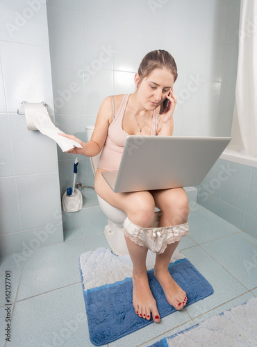 Fotografia  Funny image of woman addicted to mobile phone on toilet