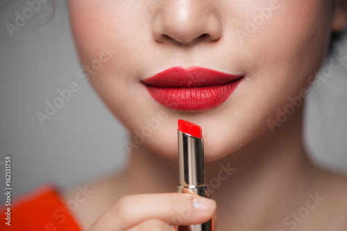 Close up portrait of attractive girl holding red lipstick over grey background Fototapet