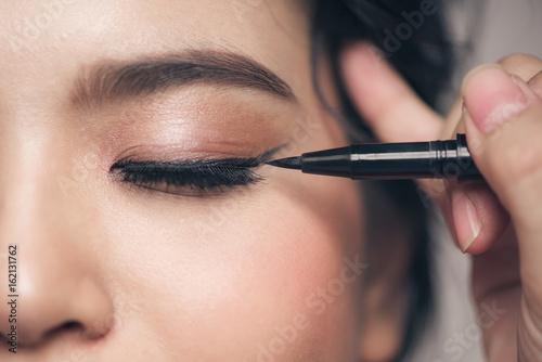 Fotografia Close-up portrait of beautiful girl touching black mascara to her lashes