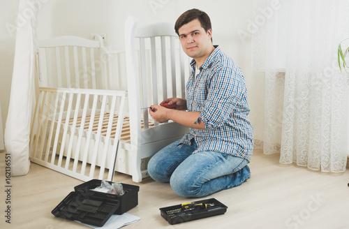 Young man disassembling furniture in nursery Wallpaper Mural