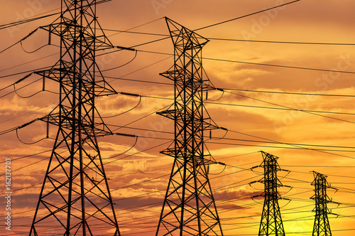 Fotografie, Obraz  Silhouette of high voltage power line cables in an orange evening sunset