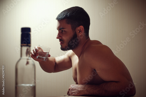 Fotografija  Young caucasian man drinking alcohol at home