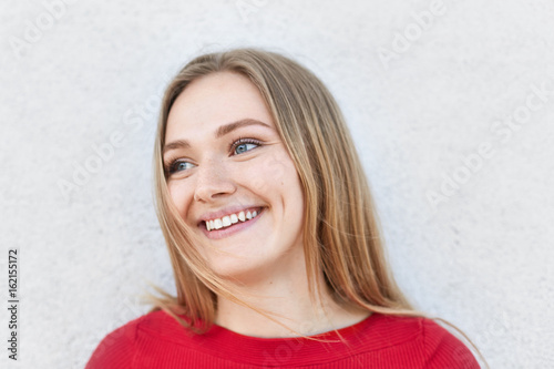 Charming female model with straight fair hair looking with her blue eyes aside having broad smile demonstrating her white teeth Tablou Canvas