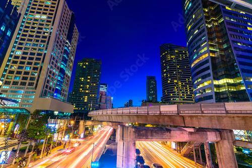 Plakat Fotografia handlowa biurowa powierzchowność. Nocny widok na dole wieżowce ze światłem pośpiechu ruchu, długie exposur w Bangkoku