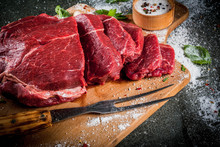 Meat. Beef, Veal. Fresh Raw Tenderloin, Piece Without Bone. For Frying Grilling Barbecue. Cut Into Steaks, Whole. On Black Stone Table,cutting Board, Spices, Salt, Fork For Meat. Top View Copy Space