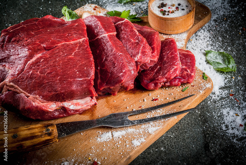 Foto op Plexiglas Vlees Meat. Beef, veal. Fresh raw tenderloin, piece without bone. For frying grilling barbecue. Cut into steaks, whole. On black stone table,cutting board, spices, salt, fork for meat. Top view copy space