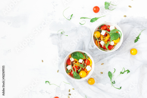 Keuken foto achterwand Vruchten Salad with arugula, feta cheese, bell pepper and cherry tomatoes. Summer vegetable salad. Flat lay, top view