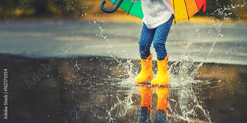 Stampa su Tela Feet of  child in yellow rubber boots jumping over  puddle in rain