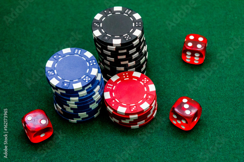Poker chips and dice on a green gaming table top view close up плакат
