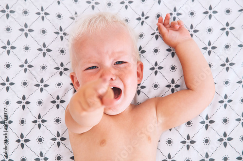 Crying angry little boy in bed. Wallpaper Mural
