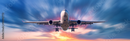 Poster Avion à Moteur Airplane with motion blur effect. Landscape with passenger airplane is flying in the blue sky with blurred clouds at sunset. Travel background. Passenger airliner. Business trip. Commercial aircraft