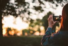 Girl Taking Photo Of Sunset